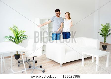 Young smiling couple showing keys to new home