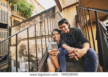 Two smiling Asian friends gathered together in urban slums and taking selfie on modern smartphone