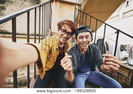 Asian teenagers in stylish clothes looking at camera with wide smiles while taking picture of themselves, shabby stairs of apartment house on background