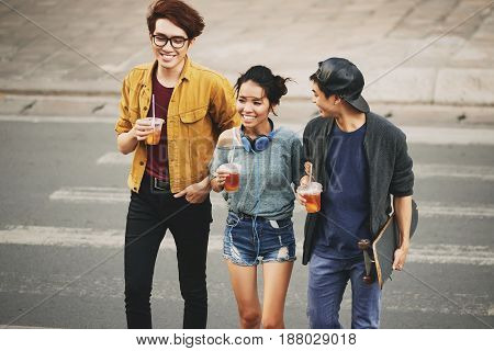 Cheerful Asian friends with plastic cups of iced tea in hands crossing street by crosswalk