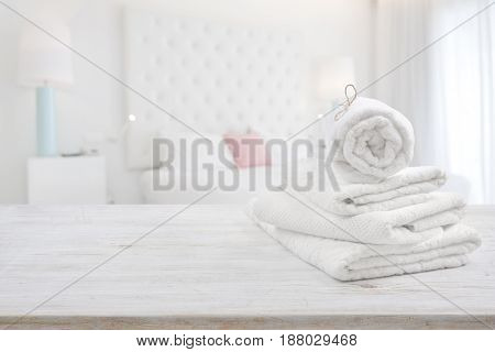 White towels on wooden surface over blurred bedroom interior background