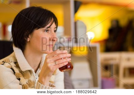 Delicate Caucasian Woman With Short Brown Hair Holding A Glass Of Tea.