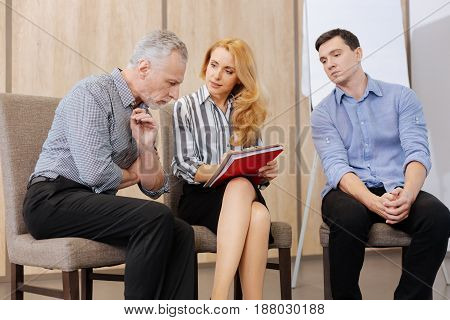What is my diagnosis. Handsome nice elderly man sitting with his psychologist and looking at her notes while wanting to know his diagnosis