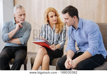 Psychological treatment. Nice handsome pleasant man sitting on the chair and listening to his psychologist while looking at her notes