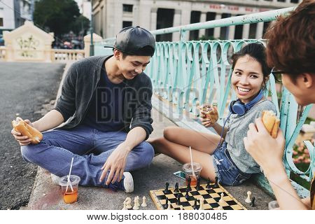 Cheerful Vietnamese friend having picnic on city bridge: they chatting animatedly, eating delicious sandwiches and playing chess