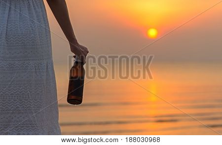 Vacation concept. Women hand holding bottle of beer in the sunset