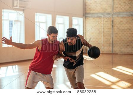 Portrait of two basketball players playing basketball in school.