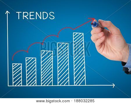 Businessman Hand Drawing Growth Trends Chart Isolated On Blue Background