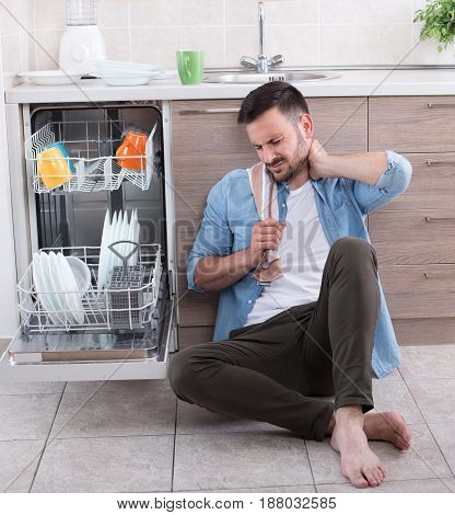 Tired Man Beside Open Dishwasher