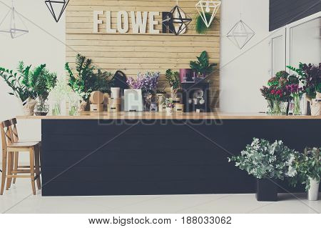 Small business. Flower shop interior. Floral design studio, decorations and arrangements. Flowers delivery service and sale of home plants in pots, wooden showcase, filtered image