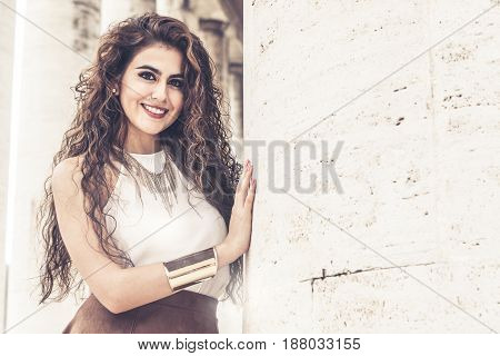 Beautiful and charming woman smiling near a marble column and building. Curly hair style. The young woman wearing sleeveless t-shirt and gold color bracelet.