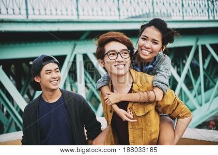 Portrait of loving young couple hanging out outdoors: handsome man in eyeglasses piggybacking his attractive girlfriend while their friend standing behind them