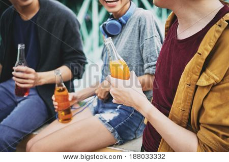 Group of cheerful friends chatting animatedly with each other while sitting on bridge railing and drinking delicious cocktails, close-up shot