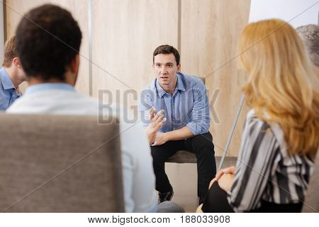 Group communication. Serious nice handsome man looking at his colleagues and gesticulating while speaking