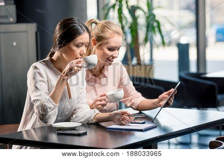 Smiling Young Women Using Digital Tablet While Drinking Coffee In Cafe, Lunch Meeting Concept