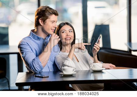 Smiling Young Woman Pointing At Smartphone And Looking At Handsome Boyfriend, Lunch Meeting Concept