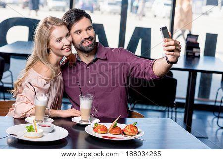 Couple In Love Taking Selfie On Smartphone On Coffee Break In Restaurant