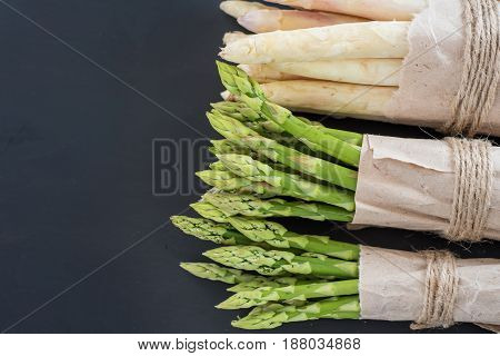 Bunches of green and white asparagus on a dark wooden background