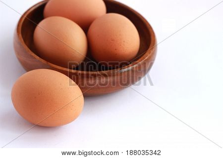Boiled eggs that are not peeled and peeled in a brown container on a white background.