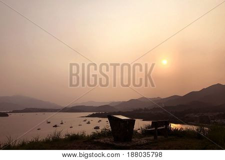 The Silhouette Of Fishing Boat, Outdoor Chair, Mountain And Sun