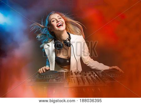 Beautiful blonde DJ girl on decks on the party on the background of orange smoke