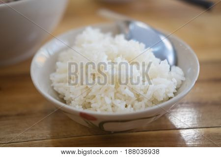 Cooked white rice in a bowl on wood table