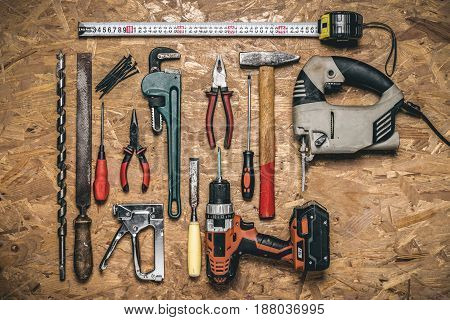 A set of hand tools for working on wood on the panel of OSB. Background. Some electric tools.