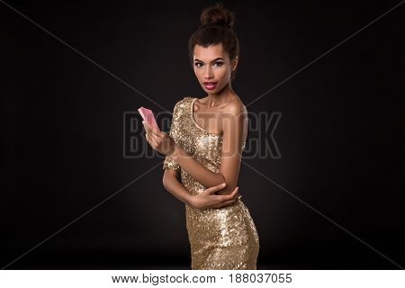 Woman winning - Young woman in a classy gold dress holding two cards, a poker of aces card combination. Studio shot on black background. Emotions poster