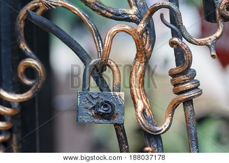 Old lock and forged fence elements closeup.