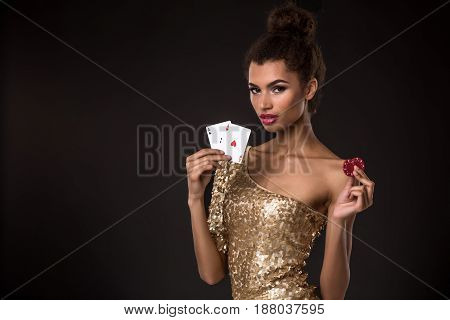 Woman winning - Young woman in a classy gold dress holding two aces and two red chips, a poker of aces card combination. Studio shot on black background