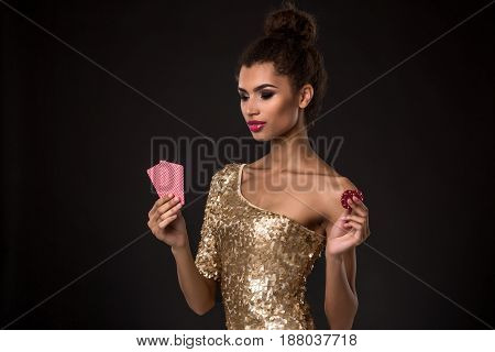 Woman winning - Young woman in a classy gold dress holding two cards and two red chips, a poker of aces card combination. Studio shot on black background