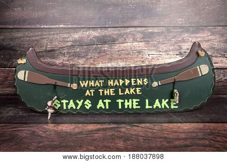A novelty canoe sign against a wood background