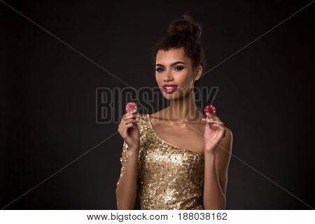 Woman winning - Young woman in a classy gold dress holding two red chips, a poker of aces card combination. Studio shot on black background poster