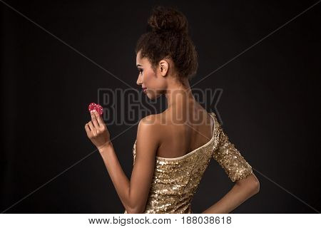Woman winning - Young woman in a classy gold dress holding two red chips, a poker of aces card combination. Studio shot on black background. A young woman stands with her back