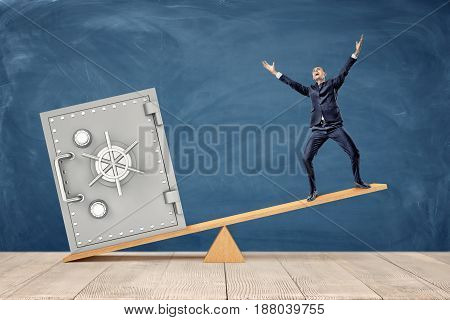 A tiny businessman standing on wooden seesaw while being overweighed by a large silver safe box. Profitable business. Positive budget. Earnings and savings.