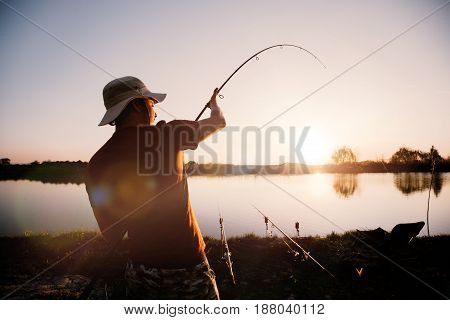 Young man fishing on lake at sunset enjoying hobby on weekend