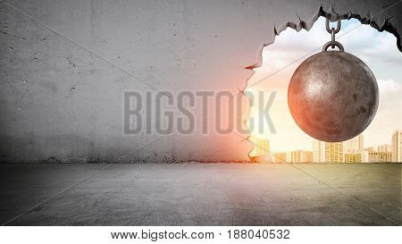 A black wrecking ball hanging inside the opening in a concrete wall showing city landscape. Old building demolition. New construction site. Freshen up your life.
