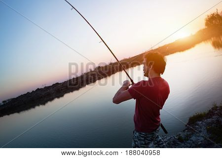 Young man fishing on lake at sunset enjoying hobby on weekend
