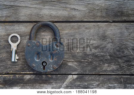 Rusty steel metal key and grungy lock on a old wooden boards background. Left position.