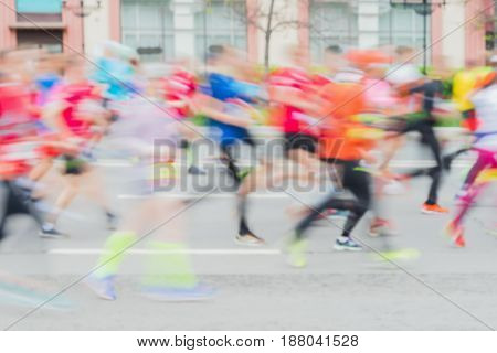 Abstract background of colored group of running athletes on the street, city marathon, blur effect, unrecognizable faces. Sport, fitness and healthy lifestyle concept. For modern backdrop, place for your text
