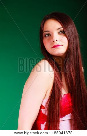 Sexuality and sensuality of women. Seductive long haired woman portrait on green background in studio.