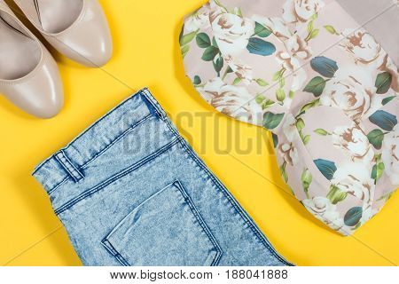 Summer feminine clothes on bright yellow background, top view