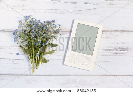 White ebook and forget me not bouquet on a white rustic wooden background