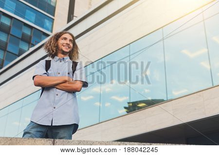 Young man standing at modern office. Smiling guy enjoy view at glass building with reflection of blue sky, copy space for text