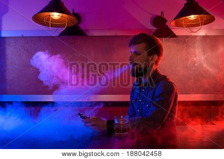 The man smoke an electronic cigarette at the vape shop. Vape bar.