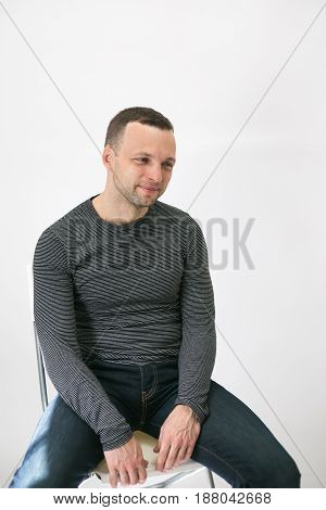 Young Adult European Man Is Sitting On A Chair