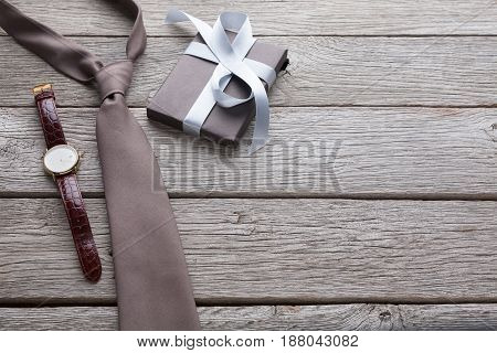 Happy Fathers Day card with copy space, present and tie on rustic wood background