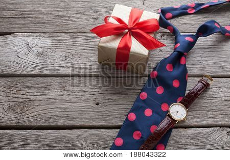 Happy Fathers Day card with copy space, present and bright spotted tie on rustic wood background
