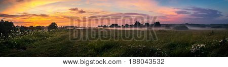 Colorful sunset at river shore meadow in deep of countryside in Russia. Panoramic view.