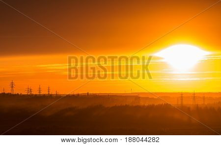 Red sunset over forest and power lines